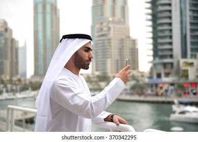 Young Emirati man taking photo or selfie with his smart phone