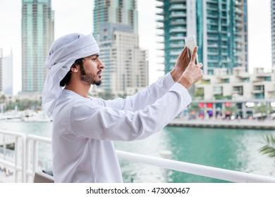 Young Emirati man taking photo or selfie, Dubai, UAE.