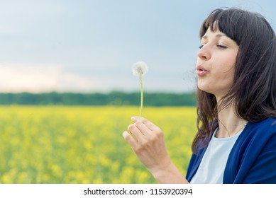 young emotional beautiful sensual pretty girl in a white shoe and in a blue cape top, with dark hair on the yellow yellow reed field with a dandelion in his hands