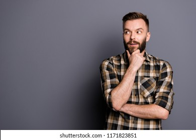 Young emotional careless man isolated on gray background with copy space for text put his head on his fist and look aside stand in casual outfit
