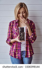 Young emotional girl while shooting with old camera on light background