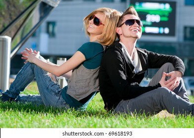 Young emotional happy teenage couple playing on grass in city park
