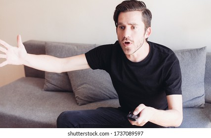 Young emotional man with a TV remote controller watching a sport football game and gesticulating with his hands
