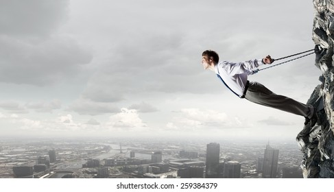 Young emotional office businessman tied with rope