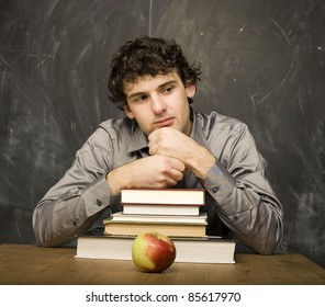 The young emotional student with the books and red apple in class room, at blackboard
