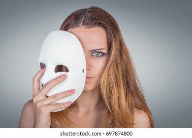 Young emotional woman holding mask in a hands
