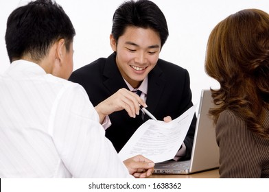 A young employee helps a couple with a form