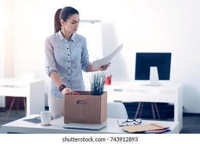 Young employee packing her stuff in box while leaving work