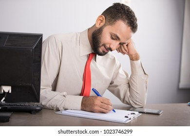 A young employee sitting on his desk writing on the clipboard focus, putting his hand on cheek,