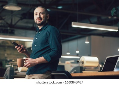 Young employee standing with a mug and a smartphone and looking into the distance. Template banner