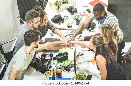 Young employee startup workers group stacking hands at urban studio during entrepreneurship brainstorming project - Business concept of human resources on working time - Start up internship at office