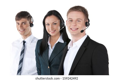 Young employee working with a headset and accompanied by his team. Standing isolated on white