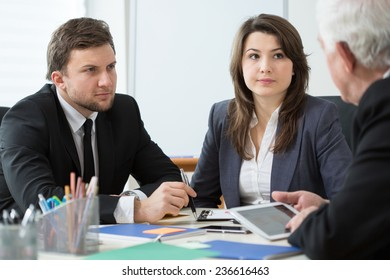 Young employees talking with boss during business appointment