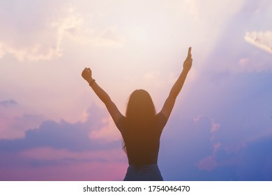 Young empowered lady raising her hands up to the sky, hand holding smart phone against sunset sky