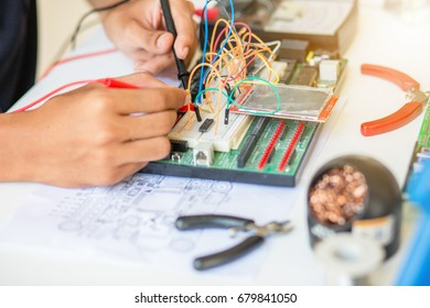 Young energetic male tech or engineer repairs electronic equipment in research facility in university.