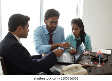 Young and energetic subordinates are discussing with boss in Indian office.  Indian corporate.