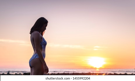 young energetic woman body wearing swimwear on a beach with sunset