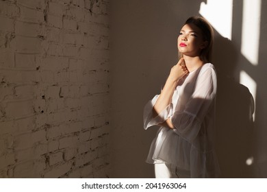 Young energy woman with a shadow pattern on body. Sun shining on wall.