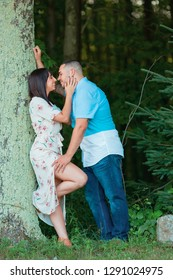 A young engaged couple enjoy a private moment in love with each other outside by tree kissing