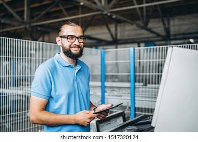 Young engeneer manager with beard checking manufactory, workplace and machinery on big factory