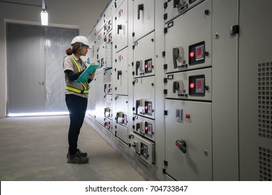 Young engineer checking status controller and multi meter of switchgear MDB distribution electrical energy substation at electical room for the industrial factory