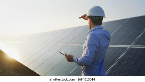 Ein junger Ingenieur überprüft mit Tablet den Betrieb von Sonne und Sauberkeit auf dem Feld der Fotovoltaik-Solarpaneele bei Sonnenuntergang. Konzept:erneuerbare Energien, Technologie, Strom, Dienstleistungen, umweltfreundliche Energie, Zukunft