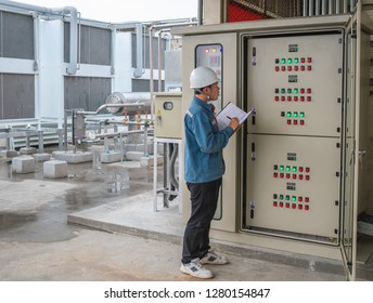 Young engineer checking temperature of refrigeration and setting temperature of compressor at control panel for cool down cool storage room in the factory