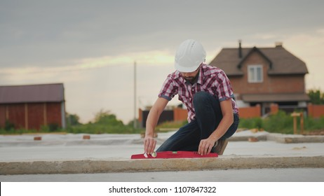 The young engineer checks the accuracy of the work on the construction of the foundation. Inspects the tilt angle of the cap. Technical control on the construction site