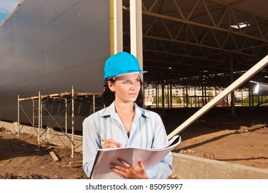 Young engineer at  construction site with building project