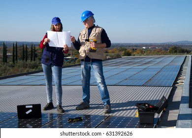 young engineer girl and an elderly skilled worker fitting a photovoltaic plant
