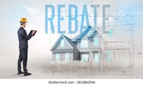 Jungingenieur, der einen Plan mit REBATE-Inschrift hält, Hausplanungskonzept