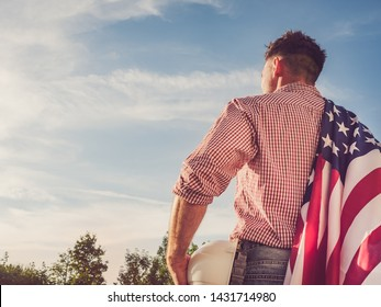 Young engineer, holding white hardhat and an American Flag in the park against the backdrop of green trees and the setting sun, looking into the distance. Close-up. Concept of labor and employment