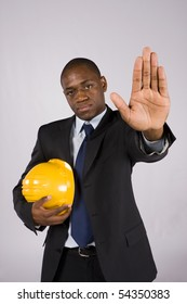 Young engineer holding a yellow helmet ordering to stop with his hand