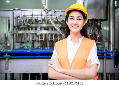 Young engineer inspecting production line. Young beautiful chinese woman in safety hat posing and smiling with bottle filling production line in background.