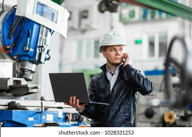 young engineer with laptop in hands talking on phone