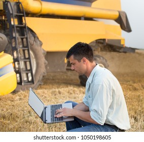 Young engineer with laptop standing in front of combine harvester in field