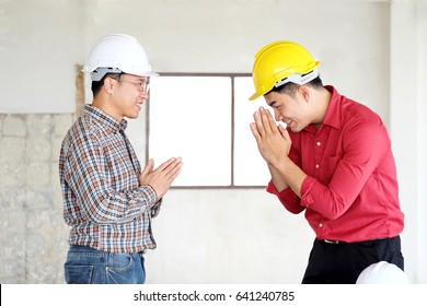 Young engineer man is greeting with posing WAI to pay respect with his boss in the morning in workplace and boss act the same with him,culture in Thailand.