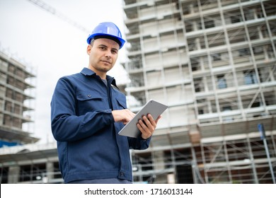 Young engineer man in suit and helmet working on tablet pc in front of a construction site