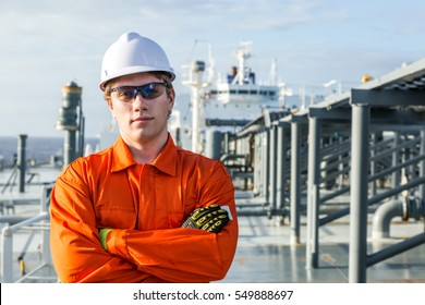 Young engineer on the deck of oil tanker.