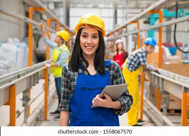 Young engineer in overalls and in work helmet looking at camera while using digital tablet