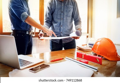 A young engineer pointing blueprint and use laptop  to explaining the design to the foreman, so that Foreman brings the house design team to the customer's needs at work. Architecture design concept.