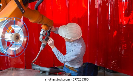 An young engineer programming and verified an industrial robot with welding system, Engineer with white helmet who checking an robot