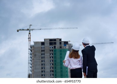 Young engineer reading blueprint at construction site.