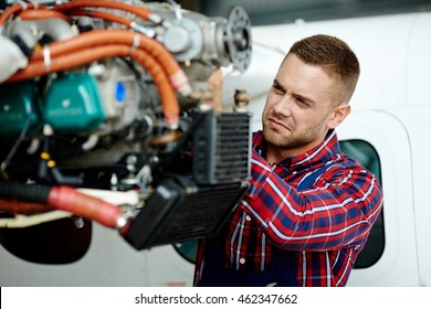 Young engineer repairing part of airplane