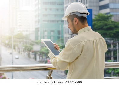 Young engineer review the project on the tablet in cityscape