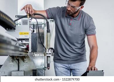 Young engineer setup plasma cutter for work in metalwork workshop.