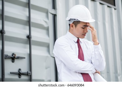 young engineer stress and thinking something, container box on background.