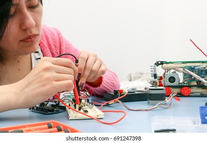 Young engineer student learning robotics and electronics