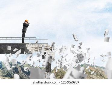 Young engineer in suit and helmet looking in binoculars while standing among flying papers on broken bridge with skyscape on background. 3D rendering.