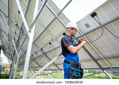 Young engineer technician making electrical wiring standing inside high exterior solar panel photo voltaic system on bright sunny summer day. Eco friendly cheap electricity generation concept.